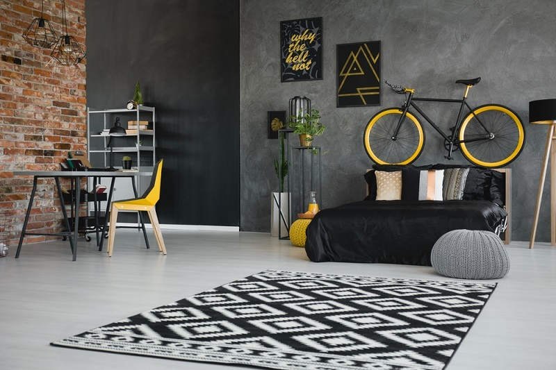 Real photo of a teenager's bedroom interior with black bed, bike on the bedhead, yellow chair at desk and geometric rug